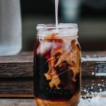 Cold brew coffee in a mason jar, milk being poured on top of it and a little bit of splashing