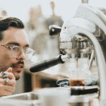A barista carefully brewing a cup of coffee